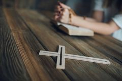 Womans hands with wooden rosary and Holy Bible Stock Image