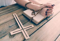 Womans hands with wooden rosary and Holy Bible Royalty Free Stock Photography