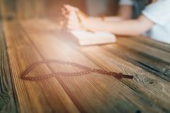 Womans hands with wooden rosary and Holy Bible Royalty Free Stock Images