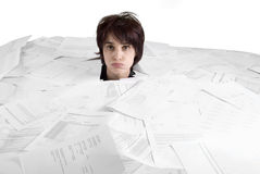 Womans head stikking out of a desk full of papers Stock Image