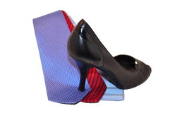 Womans High Heels Stepping on Mens Ties. Womans Black High heels stepping on 3 Multi Colored ties representing how women are dominating the business market royalty free stock image