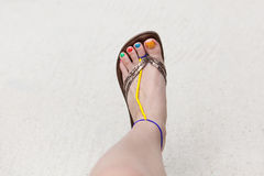 Womans leg. With painted nails on a sandy background Royalty Free Stock Image