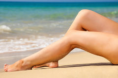 Womans  legs on the beach Stock Photography