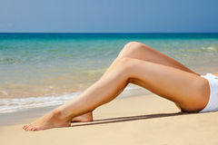 Womans  legs on the beach Stock Images