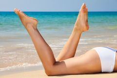 Womans  legs on the beach Stock Image