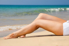 Womans  legs on the beach Stock Photos