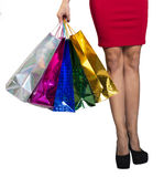 Womans legs and hand holding shopping bags Royalty Free Stock Photography