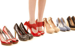 Womans legs in shoes in row of shoes Stock Photography