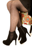 Womans legs sitting on a floral pattern chair. Womans legs in fishnet style stockings sitting on floral pattern chair wearing black heels Stock Images
