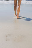 Womans legs standing on the sand Stock Image