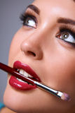 Womans lips holding make up brush Stock Image