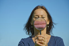 Womans lips seen through magnifying glass royalty free stock images