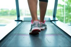 Womans muscular legs on treadmill in the gym, closeup. stock photography