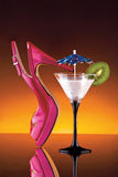Womans shoe and cocktail. A woman's pink high heel shoe and a cocktail glass garnished with a paper umbrella and a slice of kiwi Royalty Free Stock Photo