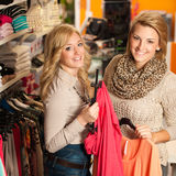 Womans shopping - Two girls in a clothes shop choo Royalty Free Stock Photo