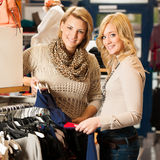 Womans shopping - Two girls in a clothes shop choo Royalty Free Stock Photography