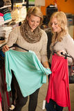 Womans shopping - Two girls in a clothes shop choosing garment Royalty Free Stock Image