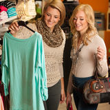 Womans shopping - Two girls in a clothes shop choosing garment Royalty Free Stock Photos