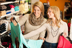 Womans shopping - Two girls in a clothes shop choosing garment Royalty Free Stock Photo