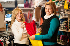 Womans shopping - Two girls in a clothes shop choosing garment Stock Photography