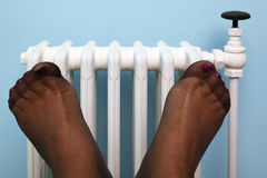Womans stocking feet in front of radiator. Photo of a woman's feet in stockings being warmed against an old traditional cast iron radiator Stock Images