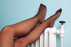 Womans stocking legs on a radiator Stock Image
