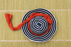 Womans summer hat on mat. Blue and white womans striped summer hat wrapped with a red cotton scarf lying on rush bathing mat womens ladys ladies ladies Royalty Free Stock Photo