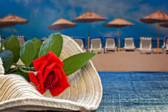 Womans summer hat with red rose with empty beach Royalty Free Stock Photos