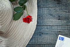 Womans summer hat with red rose and postcard Royalty Free Stock Images