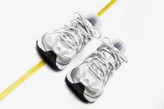 Womans trainers as a fitness concept. Womans trainers and centimeter as a fitenss concept Royalty Free Stock Photo