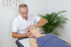 Womans visit to chiropractor. Womans visit to a chiropractor royalty free stock image