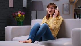 Womansitting atrativo novo no sofá, escutando a música no smartphone através dos fones de ouvido brancos grandes e filme
