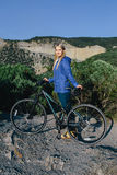 Womanstanding with the bike and enjoying life the background mountains Stock Photography