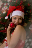 Womanwith ball next to Christmas tree stock photography