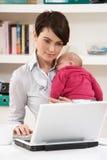 WomanWith neugeborenes Schätzchen, das vom Haus arbeitet stockbild