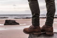 Women's Waterproof Boots and skinny trousers. Women's 6-Inch Brown Waterproof Boots and skinny trousers on a rock with sand beach and ocean in the background Stock Image