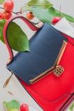 Women& à la mode x27 ; sac de s de trois couleurs du plan rapproché de peau, fond clair, décoré des pommes rouges Photos stock