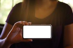 Women& x27;今后拿着手机黑屏的s手为拷贝空间屏幕 有技术概念的-图象智能手机 免版税库存照片