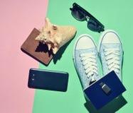 Women& x27; accesorios del viaje de s en un fondo de papel en colores pastel sneaker Imagen de archivo libre de regalías