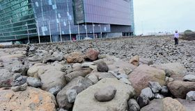 Women admiring a modern building on a rocky field. stock images