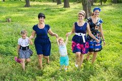 Women of all ages have fun together. Big happy family on a walk in the park. Grandmother, daughter and granddaughter walk in the spring stock photography