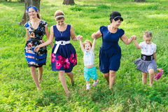 Women of all ages have fun together. Big happy family on a walk in the park. Grandmother, daughter and granddaughter walk in the spring royalty free stock photo