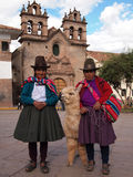 Women with alpaca in Peru. Two indigenous women in traditional clothes  with hats and an alpaca in front of a church in Cuzco in Peru Stock Image
