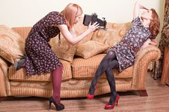 Women with antique film camera. Two young attractive blond women indoors, one posing on a settee and the other taking her picture using a retro film camera Stock Photos