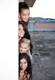 Women appearing behind the wall Royalty Free Stock Photography