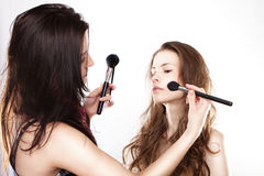 Women applying cosmetics Royalty Free Stock Images