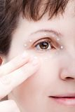 Women applying eye skin cream Stock Image
