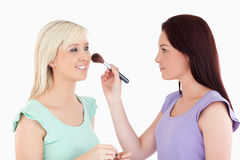 Women applying make-up. In a studio Royalty Free Stock Photo
