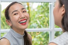 Women applying red lipstick. Beauty woman take lipstick, Girl friends helping with make-up. Girlfriends fooling around with makeup royalty free stock photos