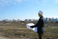 Women architect with hard hat at construction site. Women architect with blueprints and hard hat at site stock image